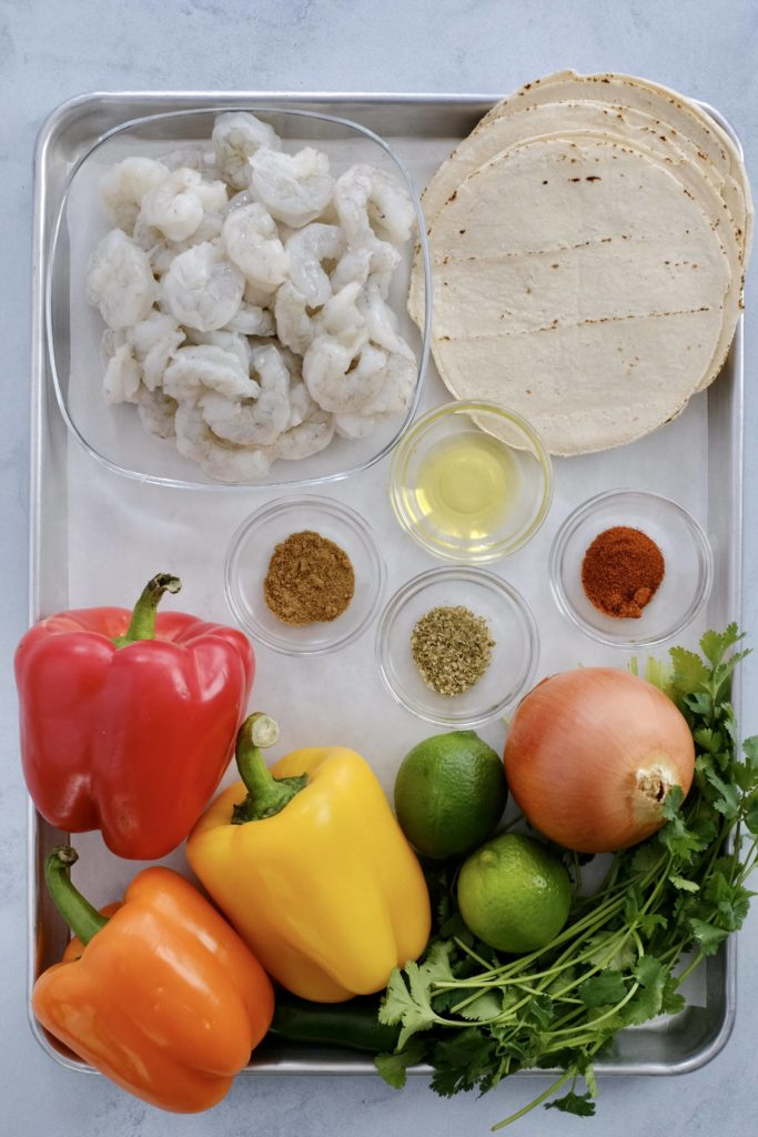 a sheet pan of raw shrimp tortilla bell peppers limes onions cilantro