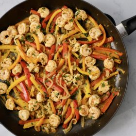 shrimp fajitas in a black skillet sitting on a white counter