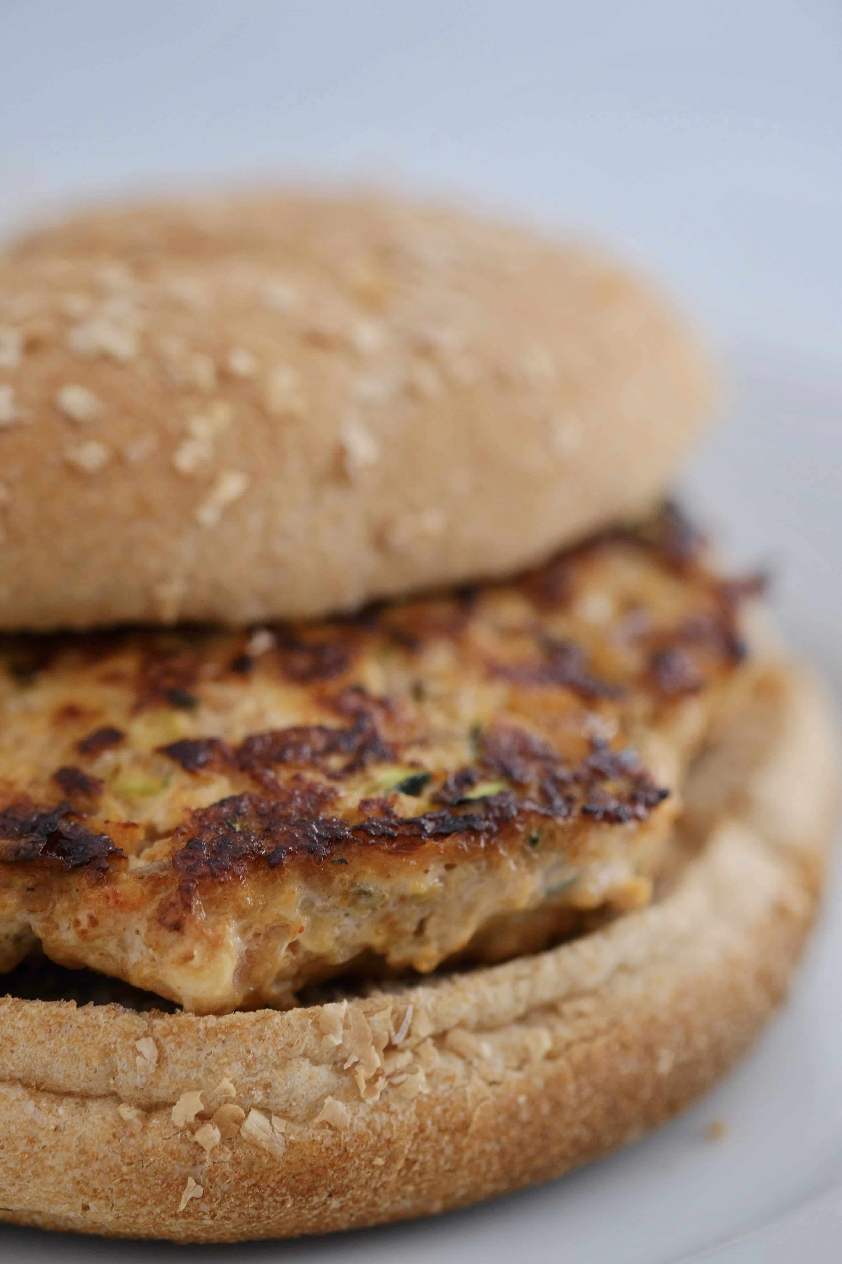 Turkey vegetable burger on a wheat bun sitting on a white plate