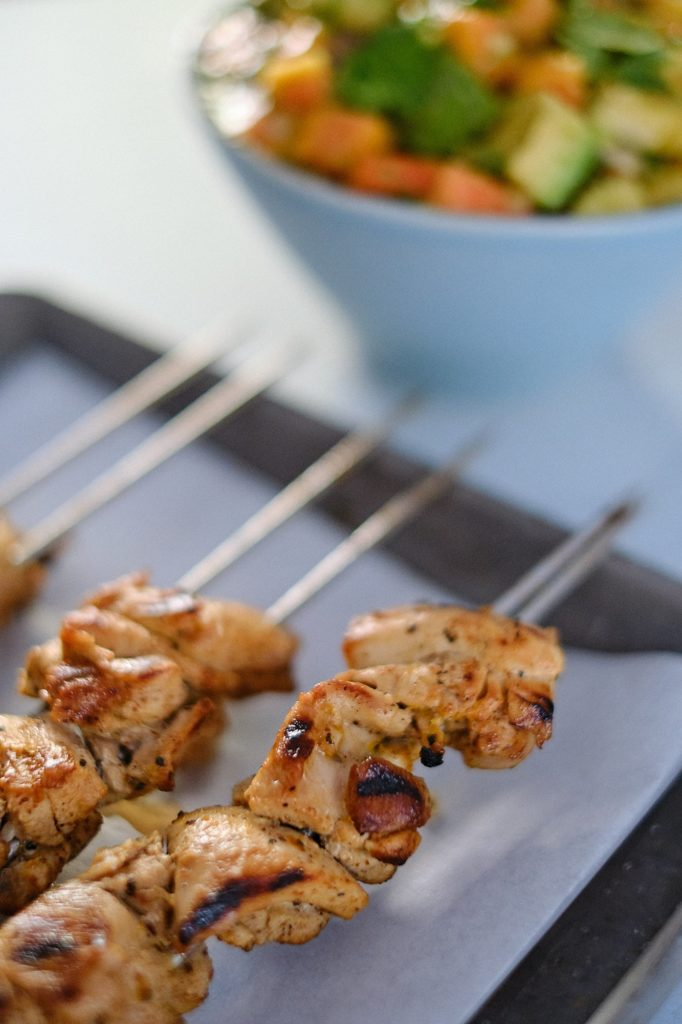 grilled chicken thighs on metal skewer with papaya avocado salad in a blue bowl