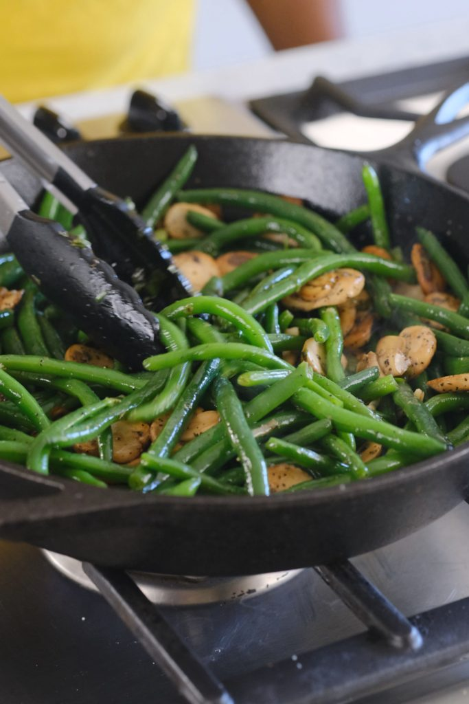 green beans and mushrooms cooking in a cast iron skillet