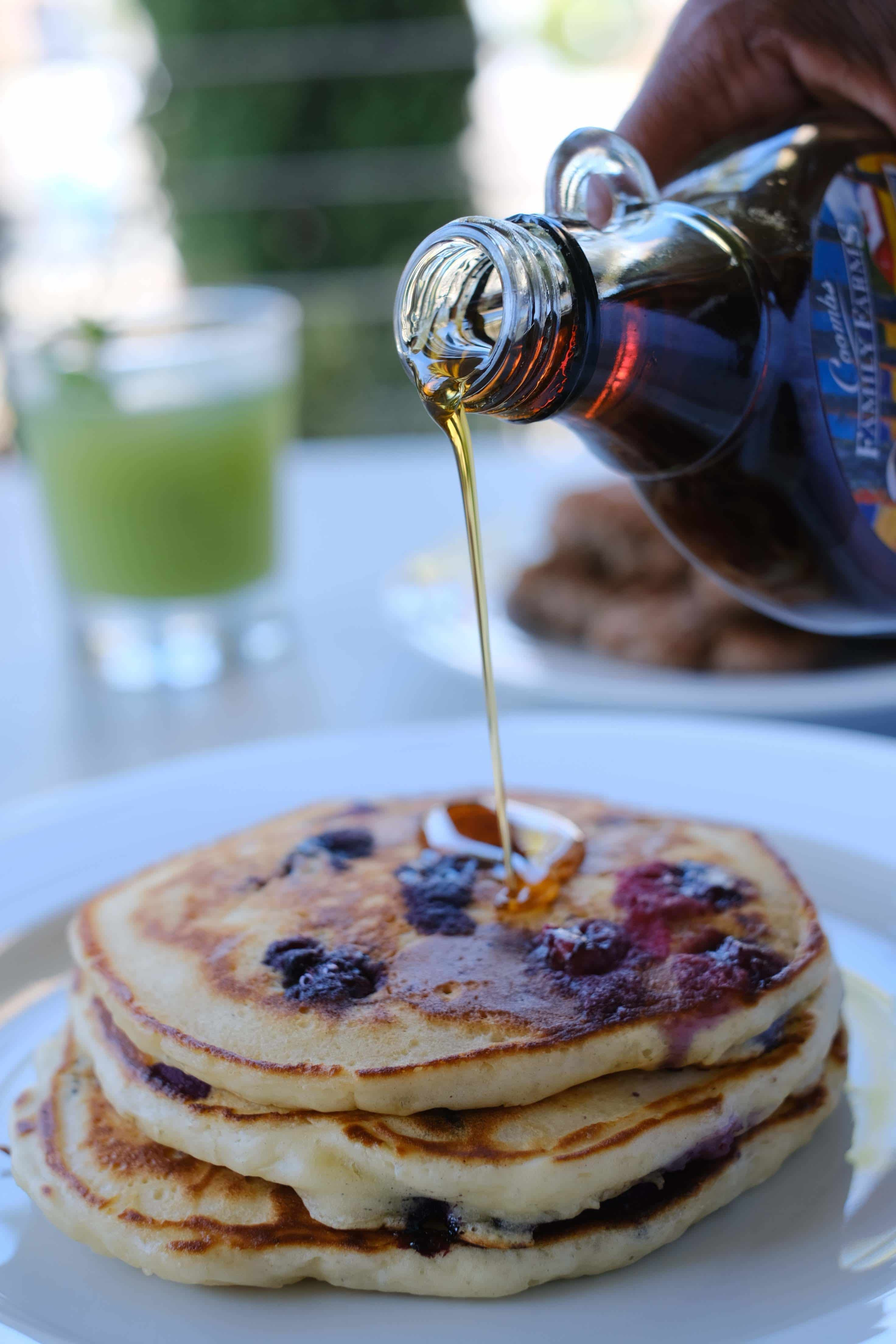 blueberry pancakes on a white plate with maple syrup pouring over them