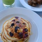 blueberry pancakes with a glass of green juice and sausage