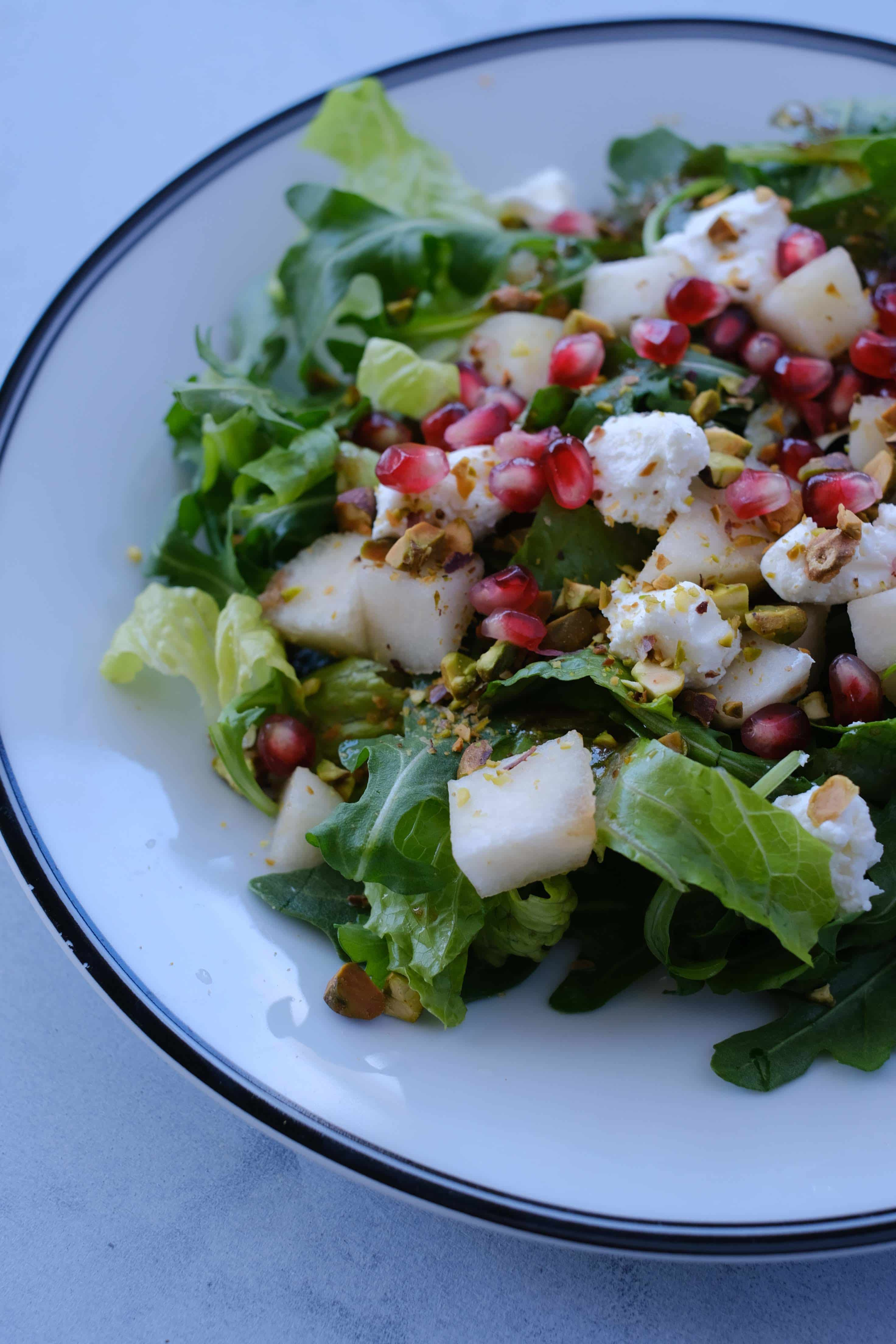 arugula salad with pomegranates on a white plate with black rim