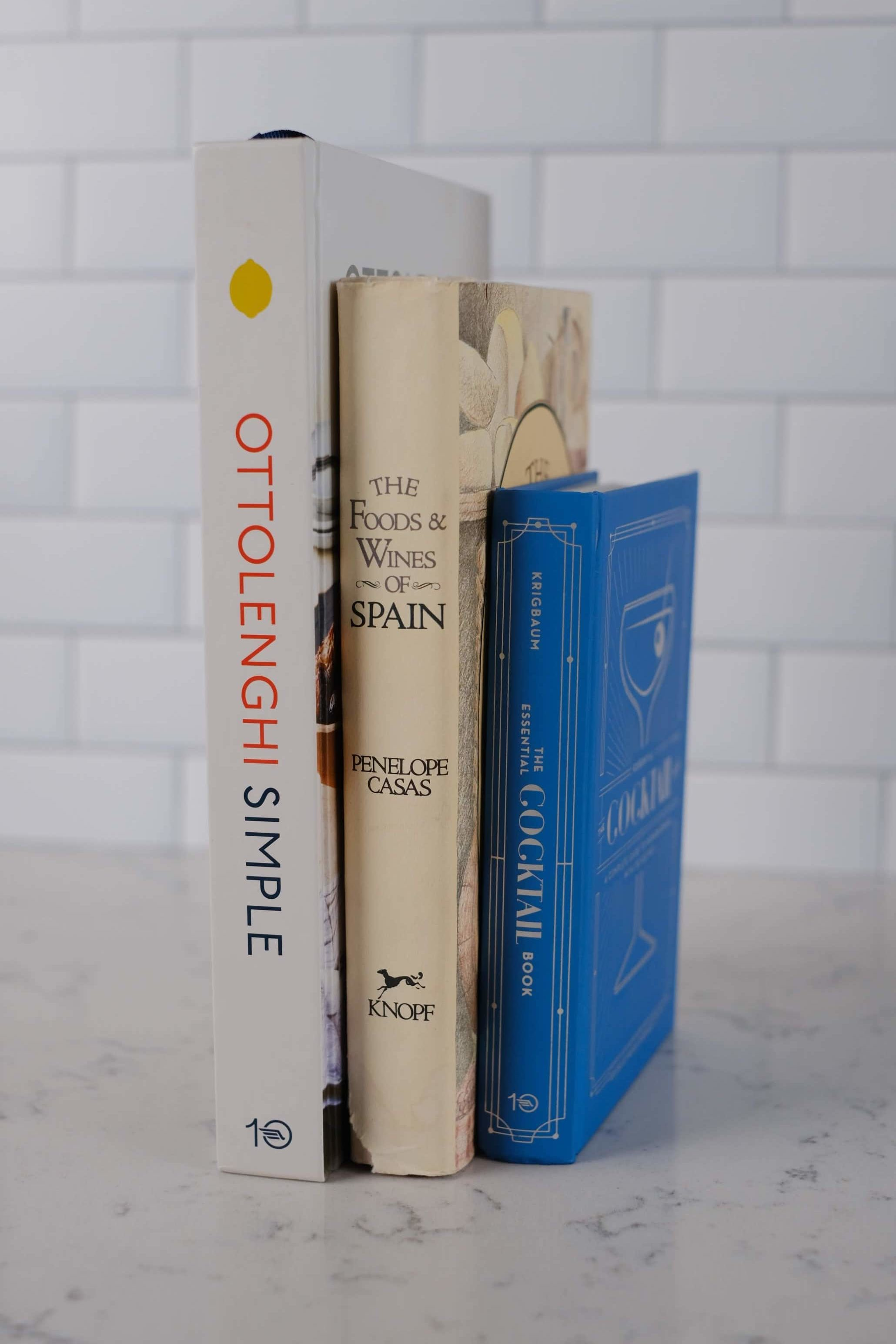 three cookbooks on marble countertop