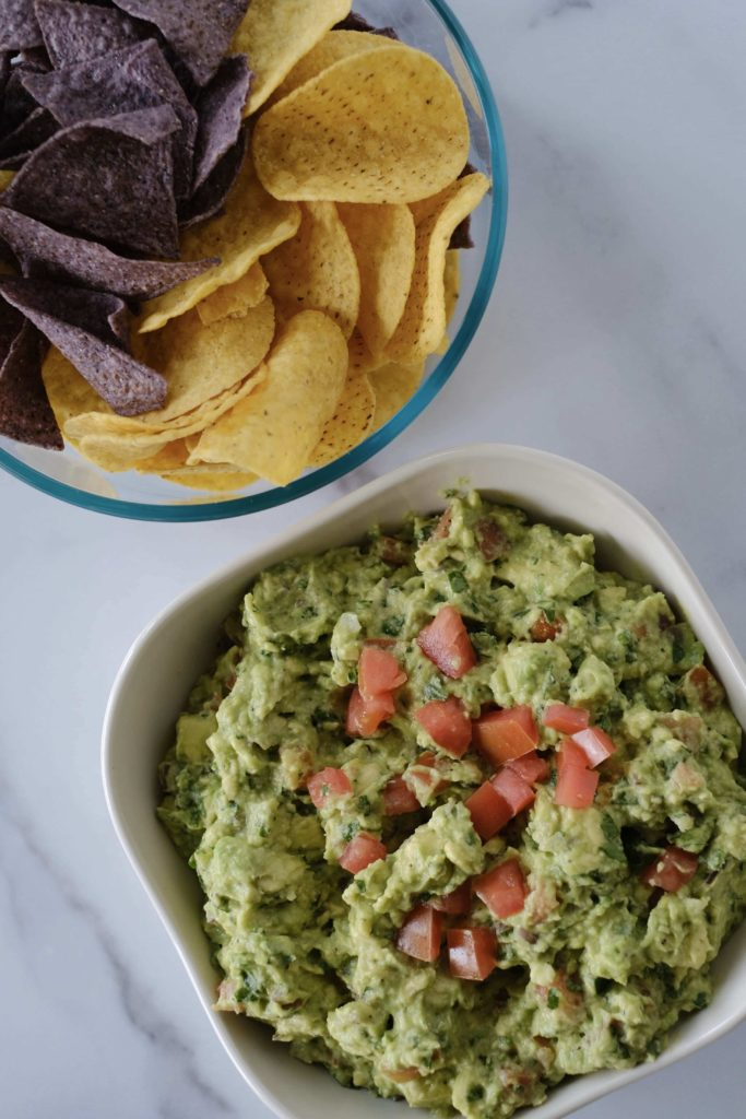 Guacamole and chips on a white table