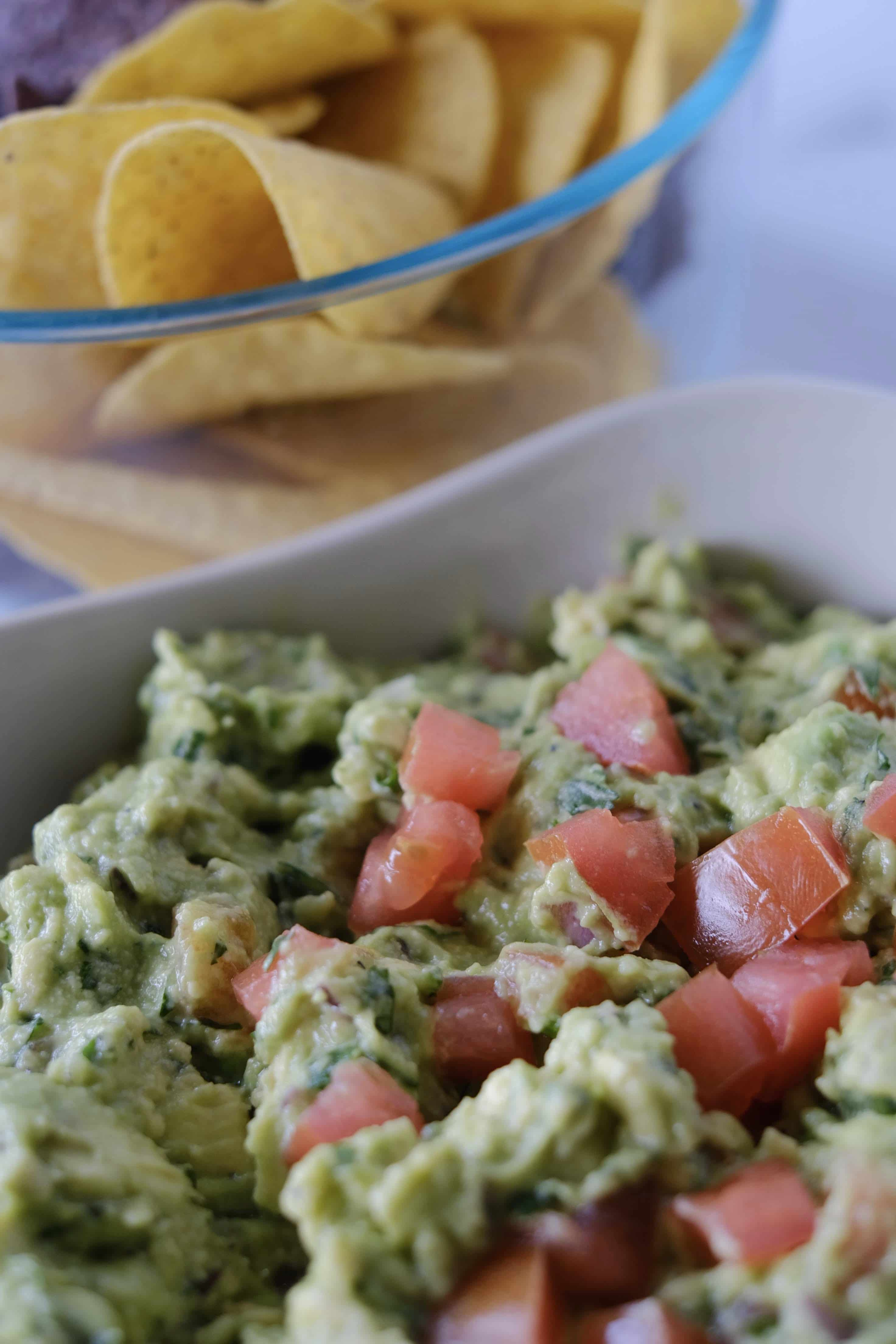 Guacamole in a bowl with chopped tomatoes on top